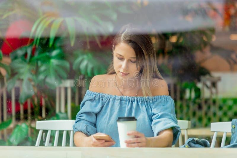 Vrouw in een een koffie en het drinken koffie en gebruiks mobiele telefoon terwijl het zitten door het venster royalty-vrije stock fotografie