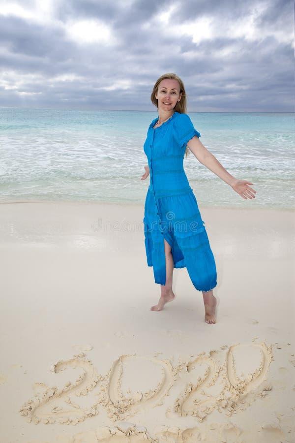Vrouw in een lange blauwe kleding naast het aantallenjaar 2020 in het zand royalty-vrije stock foto