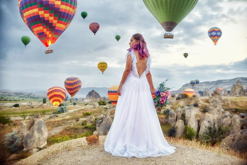Vrouw in een lange kleding op achtergrond van ballons in Cappadocia Het meisje met bloemen overhandigt tribunes op een heuvel stock afbeelding