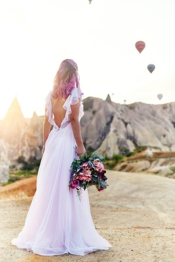 Vrouw in een lange kleding op achtergrond van ballons in Cappadocia Het meisje met bloemen overhandigt tribunes op een heuvel en  royalty-vrije stock fotografie