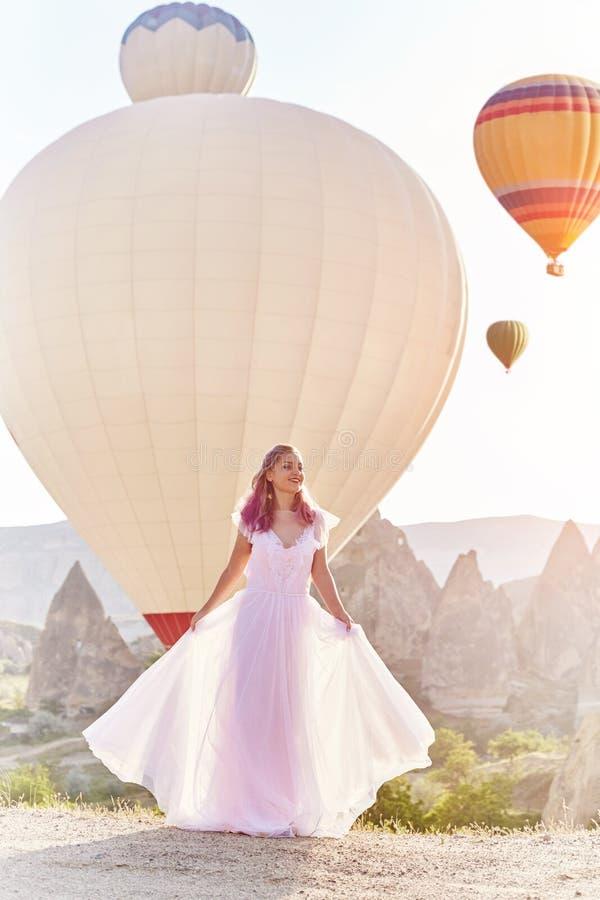 Vrouw in een lange kleding op achtergrond van ballons in Cappadocia Het meisje met bloemen overhandigt tribunes op een heuvel en  royalty-vrije stock foto
