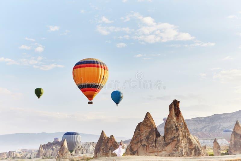 Vrouw in een lange kleding op achtergrond van ballons in Cappadocia Het meisje met bloemen overhandigt tribunes op een heuvel en  stock fotografie