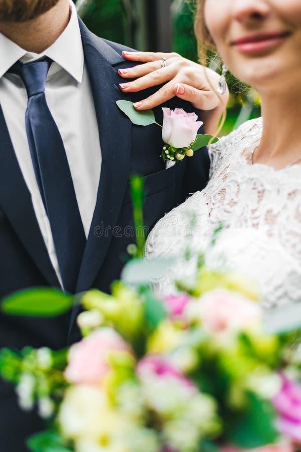 Vrouw in een lange witte kleding met een huwelijksboeket samen met een gebaarde bruidegom royalty-vrije stock fotografie