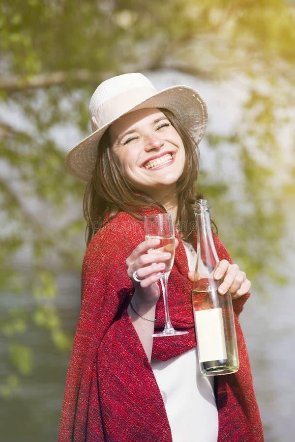 Vrouw in een rode deken wordt verpakt die een fles en een glas van cha houden die royalty-vrije stock afbeeldingen