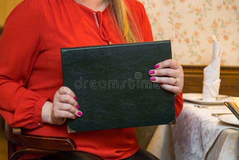 Vrouw in een rode kleding die menu in hand dichte omhooggaand houden royalty-vrije stock foto's