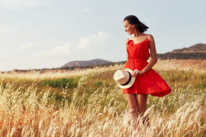 Vrouw in een rode kleding die op het gebied op een warme de zomeravond lopen Geel gras bij zonsondergang, het meisje die een hoed royalty-vrije stock fotografie