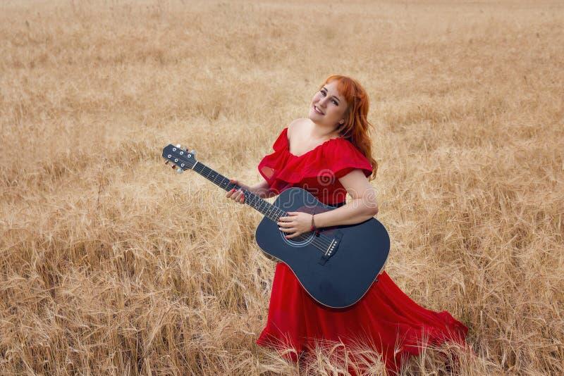 Vrouw in een rode kleding met een gitaar op een gerstgebied royalty-vrije stock foto