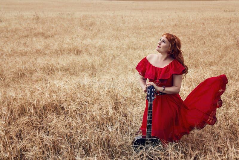 Vrouw in een rode kleding met een gitaar op een gerstgebied royalty-vrije stock afbeelding