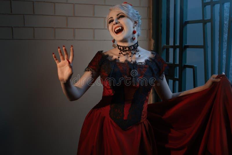 Vrouw in een rode kleding met een vampiergrijns royalty-vrije stock fotografie