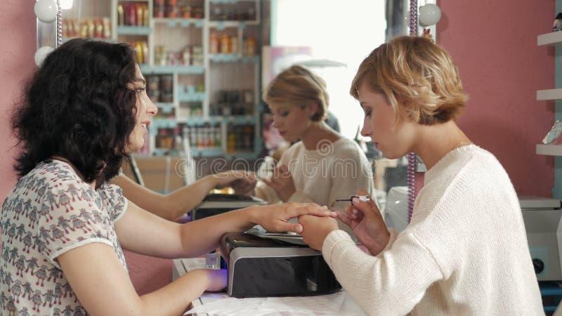 Vrouw in een spijkersalon die manicure door schoonheidsspecialist met dossier ontvangen getting spijkers aan klant vaag stock fotografie