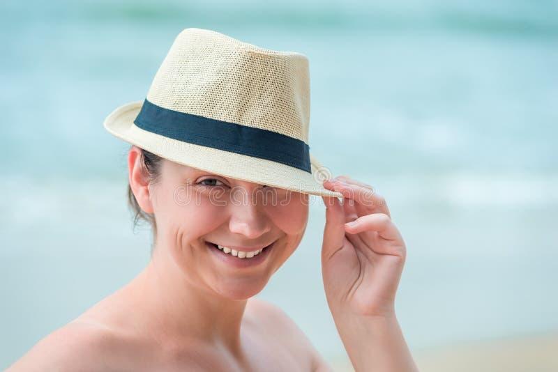 Vrouw in een strohoed die, portret op het strand glimlachen stock fotografie