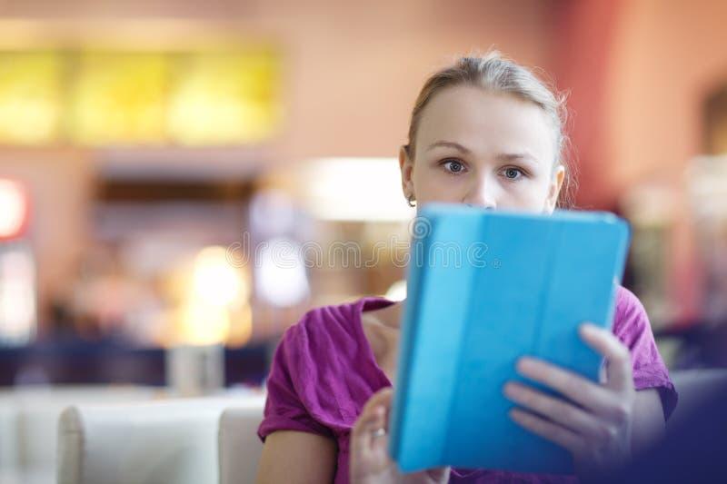 Vrouw in een terminal die haar tablet gebruiken royalty-vrije stock foto