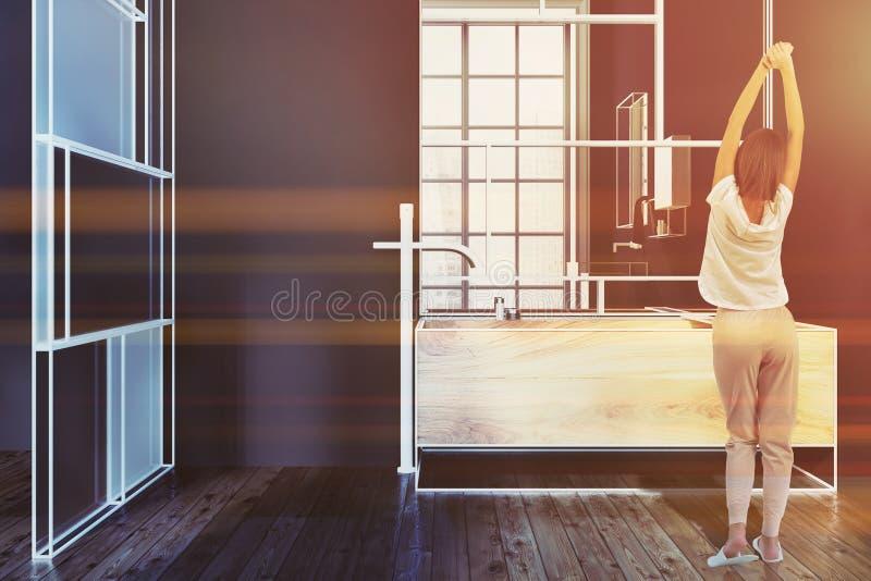 Vrouw in een ultra modern zwart badkamersbinnenland stock foto's