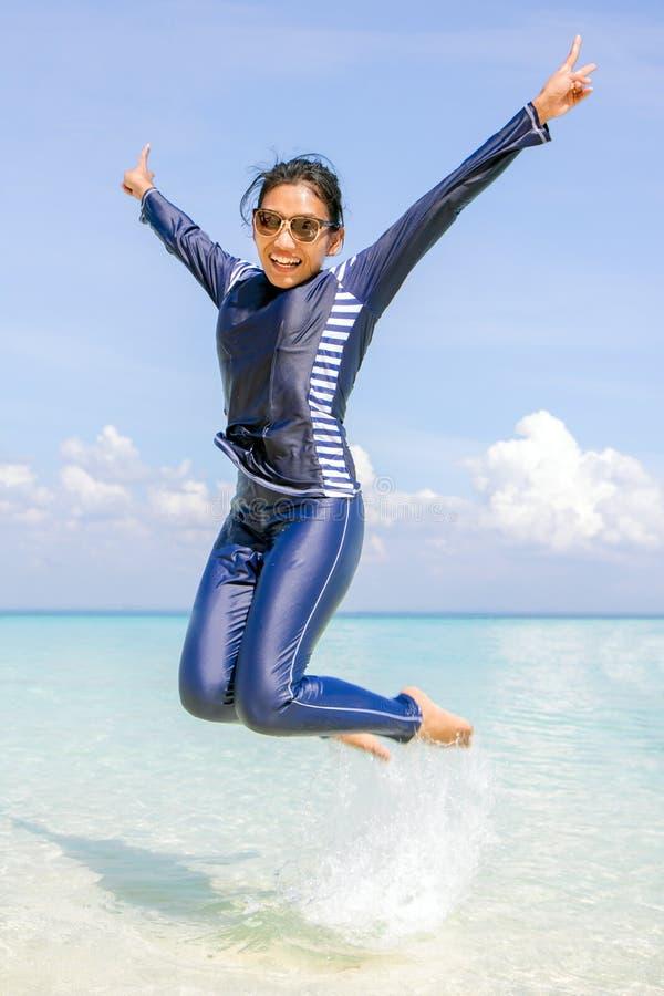 Vrouw in een volledig-lichaamszwempak op het Overzees is gesprongen die stock afbeelding