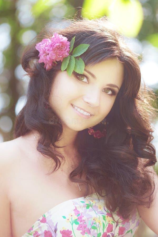 Vrouw in een weelderige tuin met bloemen royalty-vrije stock foto