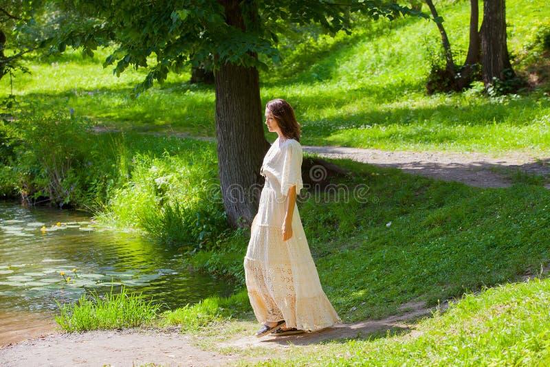 Vrouw in een witte kleding in een de zomerpark stock afbeelding