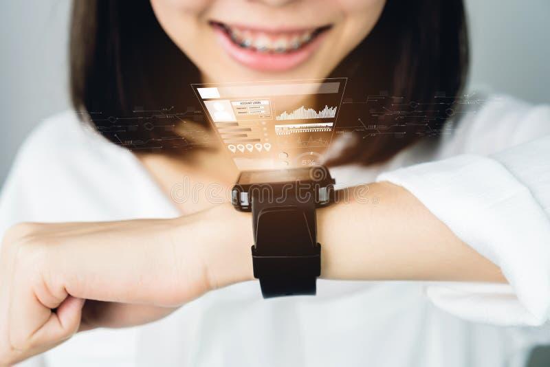 Vrouw in een witte kleding die een digitale klok vooraf vertoning en technologiein mededeling gebruiken Dit is een nieuwe technol stock afbeeldingen