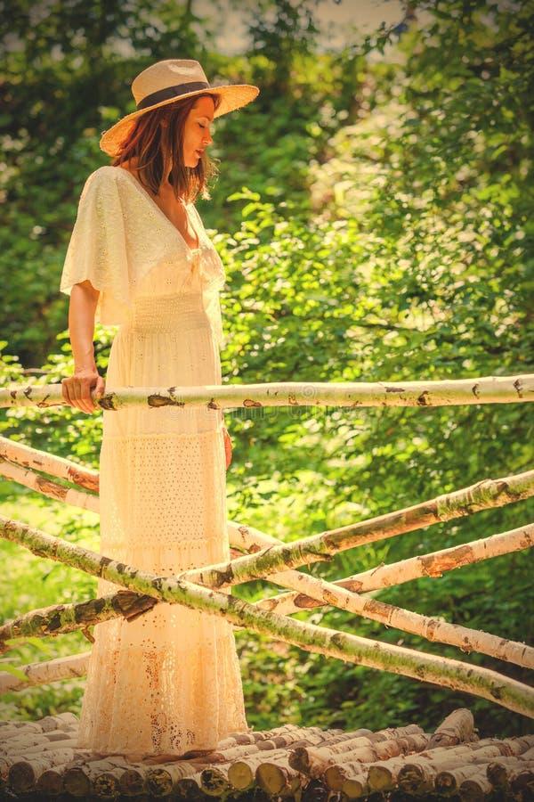 Vrouw in een witte kleding en een de zomerhoed op een brug van een berk stock afbeelding