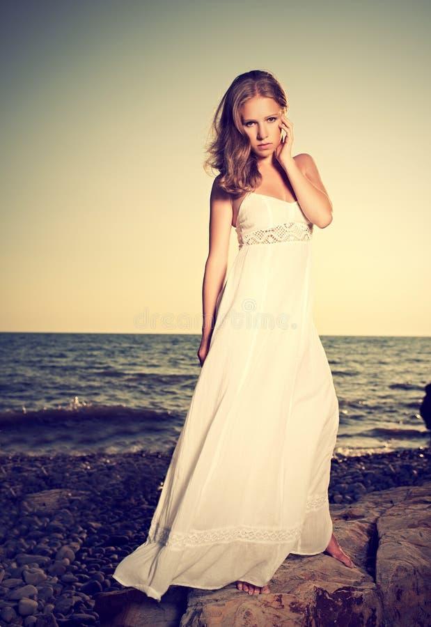 Vrouw in een witte kleding op het strand door het overzees stock afbeelding