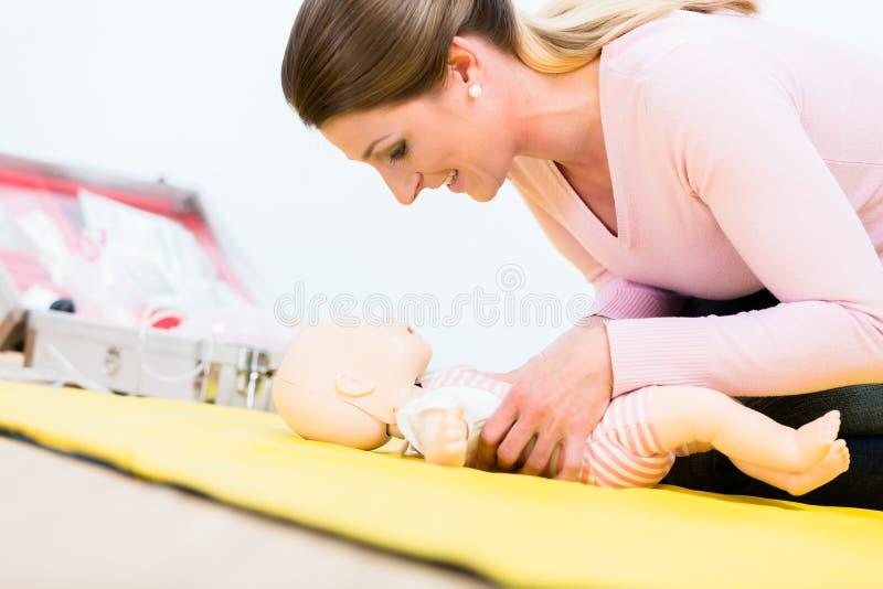 Vrouw in eerste hulpcursus het praktizeren heropleving van zuigeling op baby D royalty-vrije stock fotografie