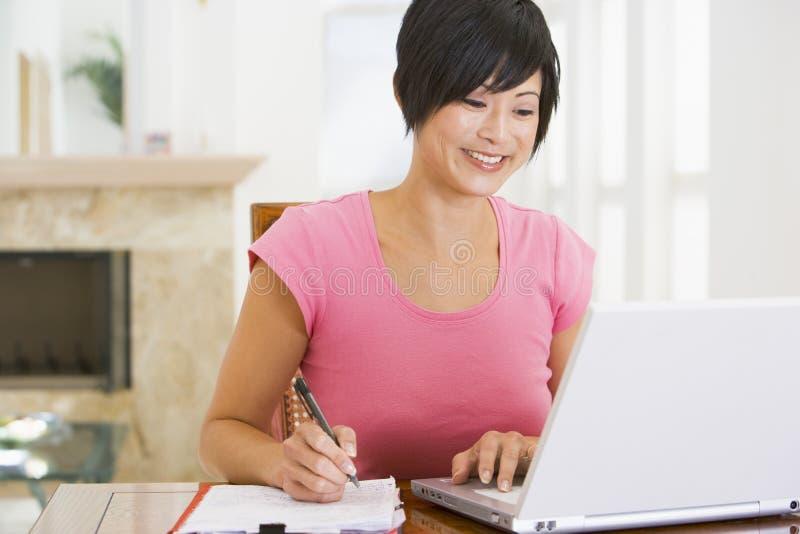 Vrouw in eetkamer met laptop het glimlachen royalty-vrije stock foto's
