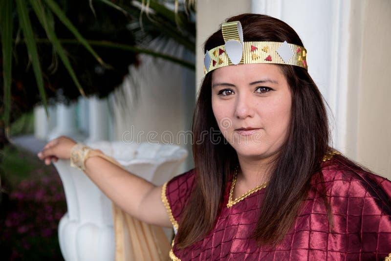 Vrouw in Egyptisch prinseskostuum die op vaas leunen stock afbeelding