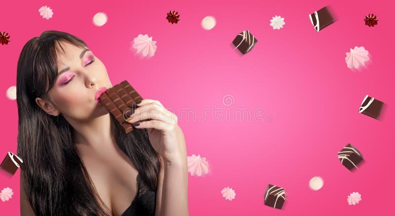 Vrouw en chocolade De mooie jonge vrouw eet chocolade o stock afbeeldingen