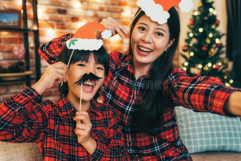 Vrouw en dochter met zwarte snor die pret hebben stock foto's