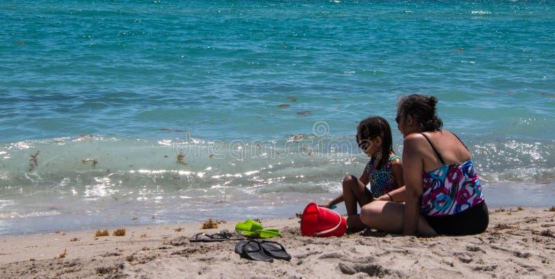 Vrouw en dochter op strand stock afbeeldingen