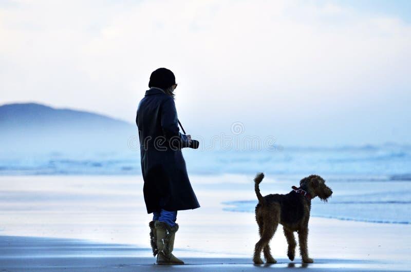 Vrouw en gelovige vriendenhond alleen bij het overweldigen van strand het letten op oceaan stock fotografie