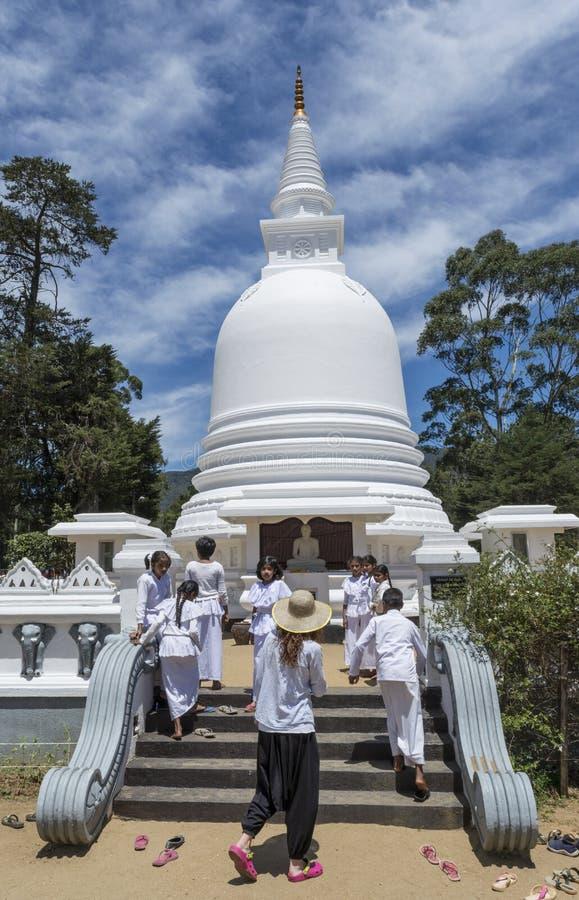 Vrouw en groep kinderen in eenvormig op de treden bij de witte boeddhistische stupabouw die in de stad van Nuwara wordt gevestigd royalty-vrije stock foto's