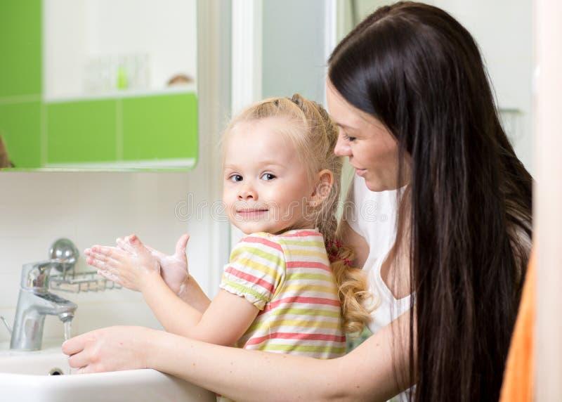 Vrouw en haar handen van de het meisjeswas van het dochterjonge geitje met zeep in badkamers royalty-vrije stock foto
