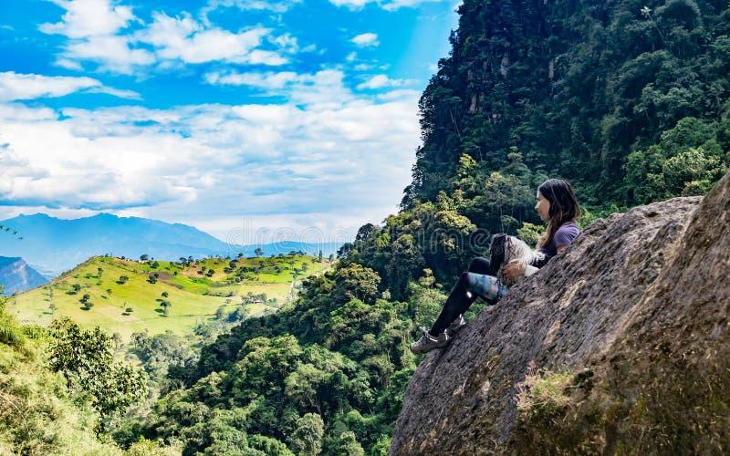 Vrouw en haar hond die de horizon op een rots, tweede ph overwegen stock foto's