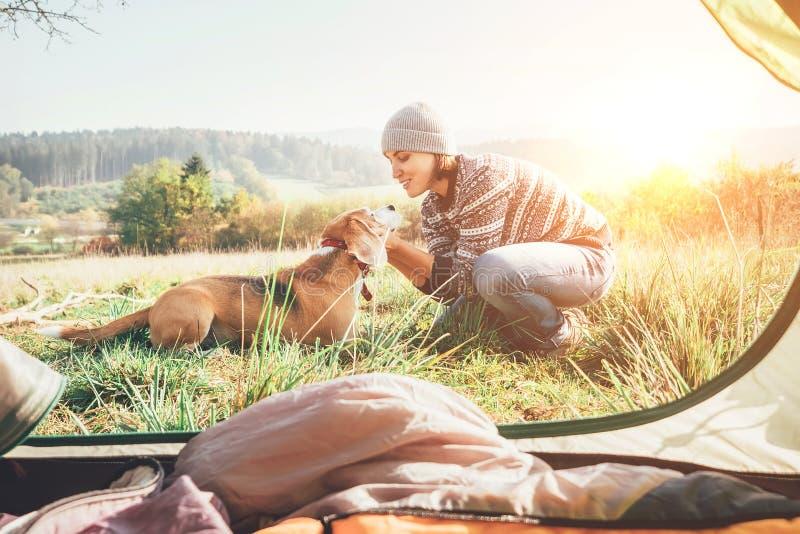 Vrouw en haar hond tedere scène dichtbij de het kamperen tent Actieve vrije tijd, die met beeld van het de dingenconcept van pet6 royalty-vrije stock afbeeldingen