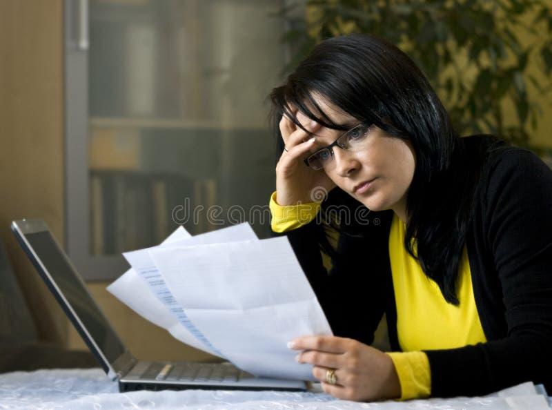 Vrouw en haar maandelijkse rekeningen stock fotografie