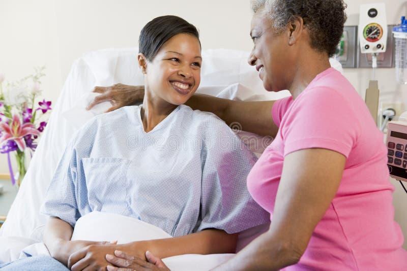 Vrouw en Haar Moeder die in het Ziekenhuis spreken royalty-vrije stock afbeelding