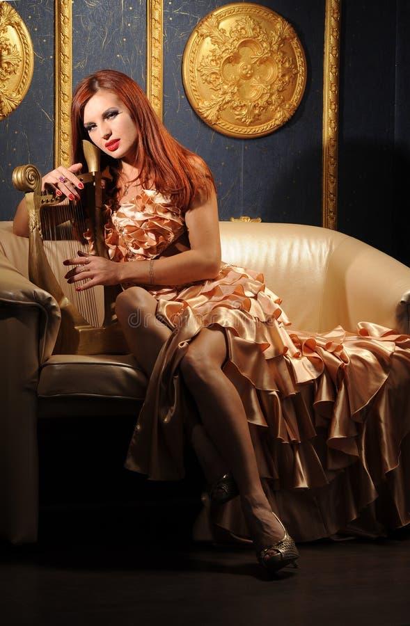Vrouw en harp stock afbeeldingen