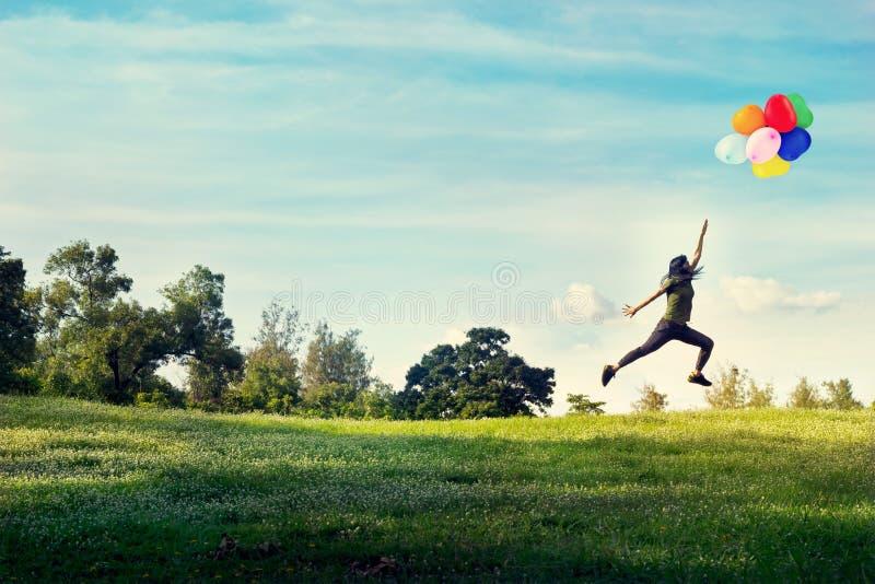 Vrouw en het springen aanrakingsballons die in de hemel op groen gras en bloemgebied drijven lopen stock afbeeldingen