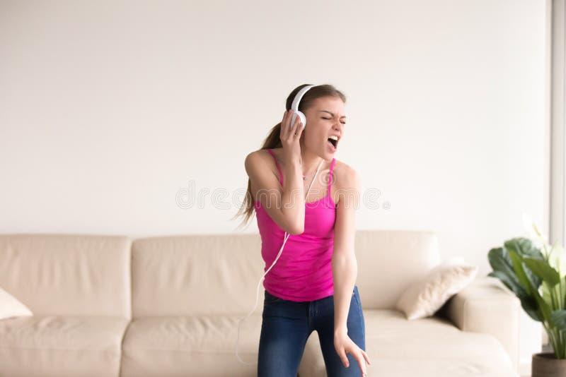 Vrouw in en hoofdtelefoons die thuis zingen dansen royalty-vrije stock afbeelding