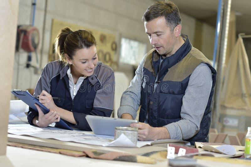 Vrouw en instructeur in timmerwerkworkshop stock fotografie