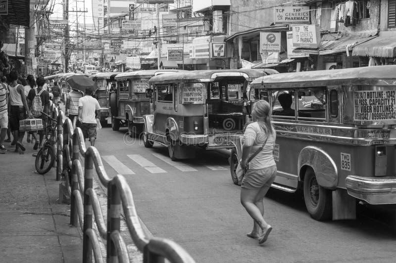 Vrouw en Jeepneys in Quezon stock foto