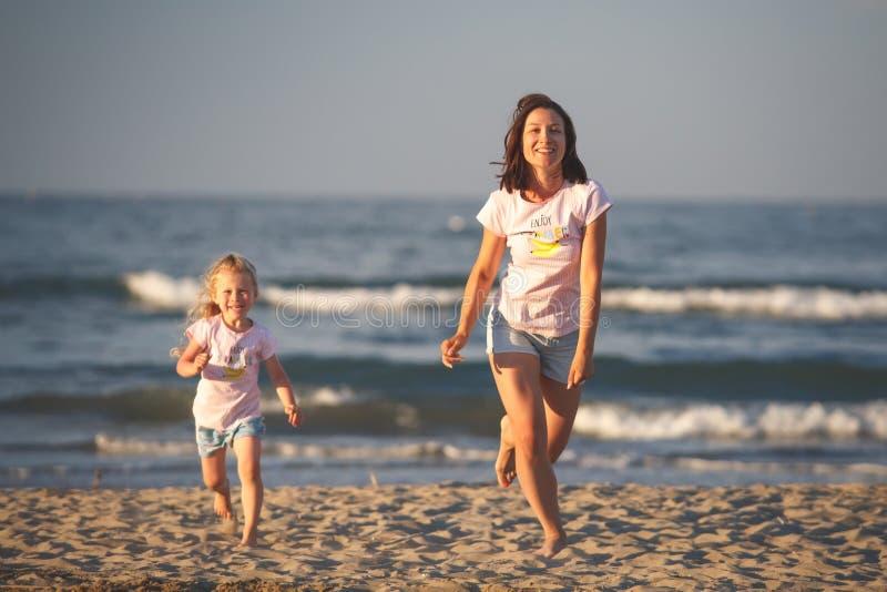 Vrouw en jong geitje op strand stock fotografie