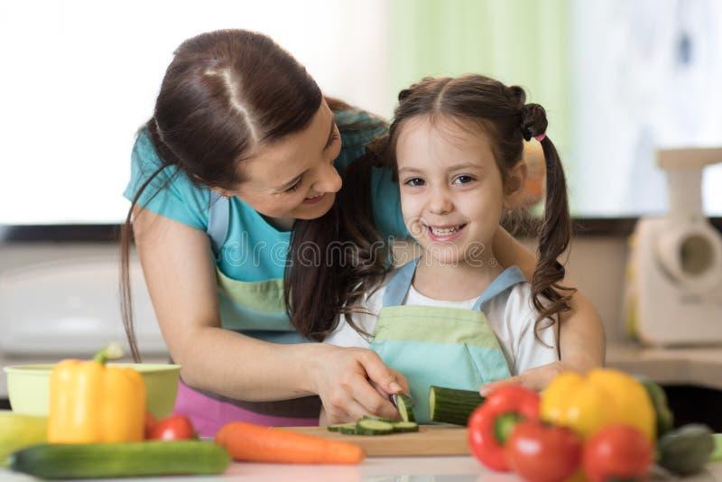 Vrouw en jong geitjemeisje die een groentensalade in de keuken voorbereiden stock afbeeldingen