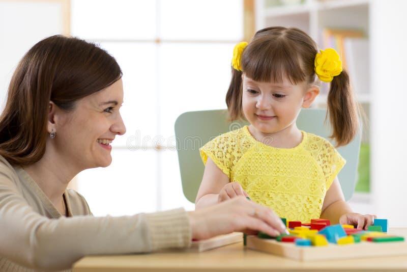 Vrouw en jong geitjemeisje die logisch speelgoed thuis spelen royalty-vrije stock afbeelding