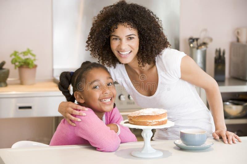 Vrouw en jong meisje in keuken met cake en coff royalty-vrije stock fotografie
