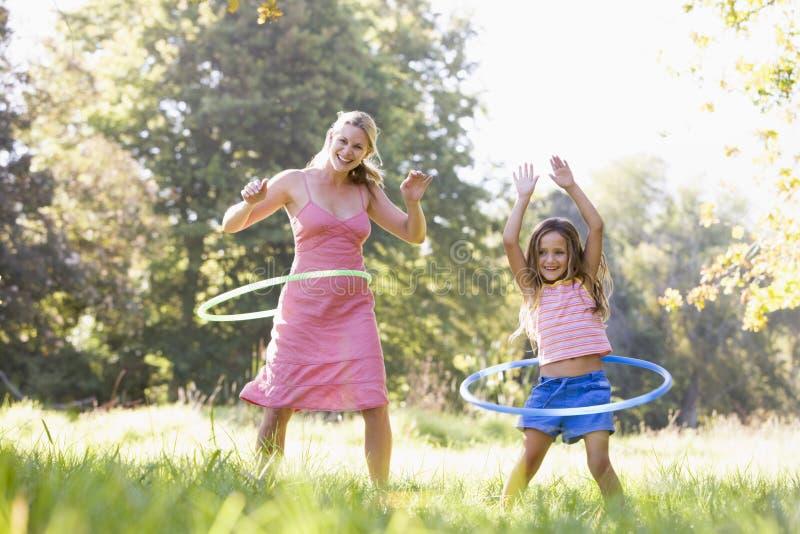 Vrouw en jong meisje met hulahoepels het glimlachen stock foto's