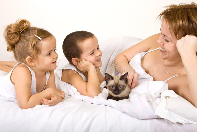 Vrouw en jonge geitjes met een katje dat in het bed lazying stock foto's