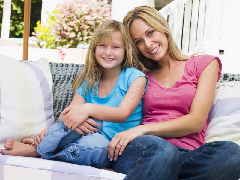 Vrouw en jonge meisjeszitting bij terras het glimlachen royalty-vrije stock afbeeldingen