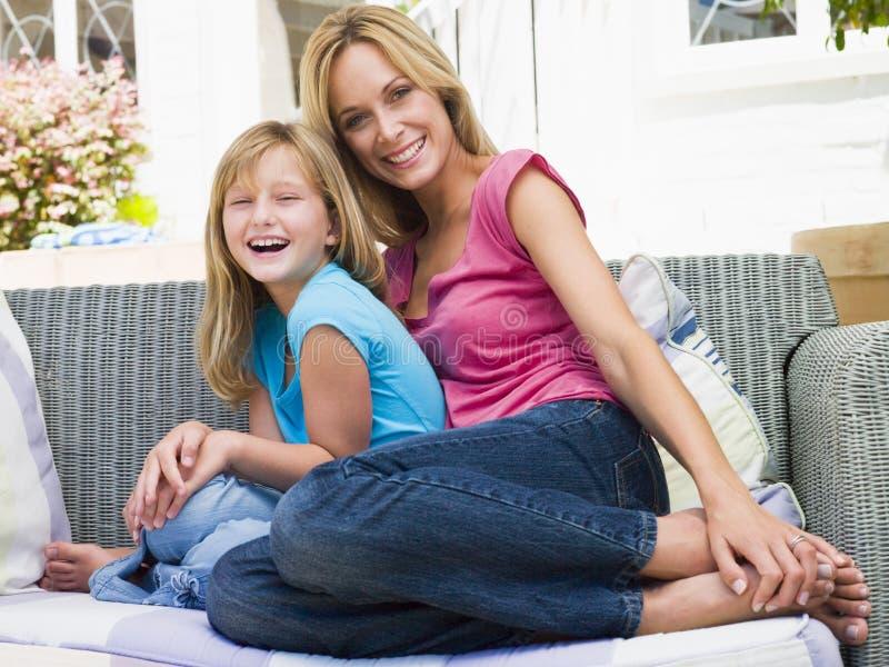 Vrouw en jonge meisjeszitting bij terras het glimlachen stock foto's