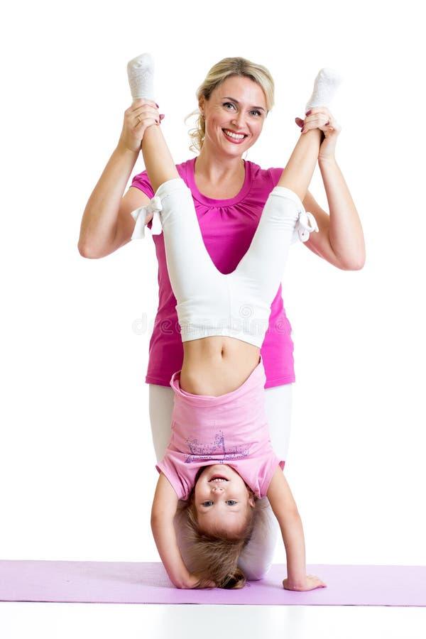 Vrouw en kid daughter do yoga oefening bij mat stock afbeelding